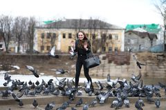 Girl on a walk in the park and a flock of pigeons stock image