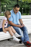 Girl on a walk in the park with her father. Girl with her father sitting on the bench in the park Royalty Free Stock Photography