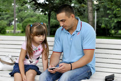 Girl on a walk in the park with her father. Girl with her father sitting on the bench in the park Stock Images