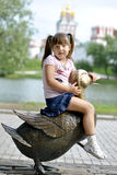 Girl on a walk in the park. Girl sitting on the big copper duck in the park Stock Photography