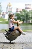 Girl on a walk in the park. Girl sitting on the big copper duck in the park Royalty Free Stock Images
