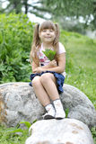 Girl on a walk in the park. Girl sitting on a large rock in the park Stock Photo