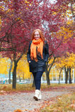 Girl walk on pathway in city park with red trees, fall season Stock Photos
