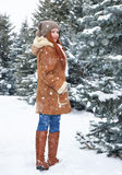 Girl walk in winter park at day. Fir trees with snow. Redhead woman full length. Royalty Free Stock Photo