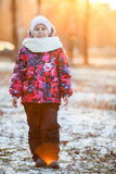 Girl on a walk in winter park in the rays of setting sun, looking at the camera Royalty Free Stock Photos