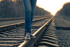 Girl walking across railroad. Warm color toned image Stock Image