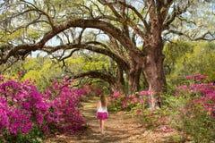 Girl walking alone in the beautiful blooming garden under oak trees. Stock Photos