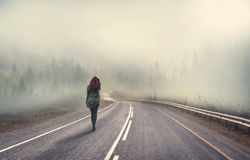 Girl walking alone. On mountain highway in winter foggy day royalty free stock photography
