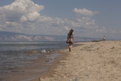 Girl walking along the beach Stock Photography