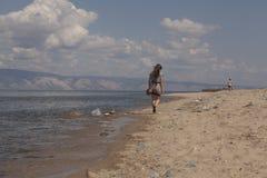 Girl walking along the beach Stock Photography