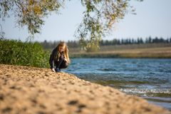 Girl walking along the beach. Girl goes along the beach in the autumn day stock images