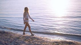 The girl is walking along the beach at sunset. Out of focus, good for background. Slow motion. stock footage