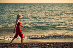 Girl walking along the beach. Vintage look royalty free stock photos