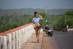 The girl is walking along the bridge on the background of a moto. The girl is walking across the bridge on the background of a motorcycle, dressed in a topic and Stock Images