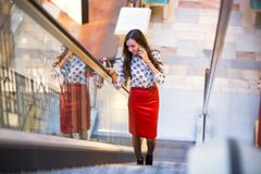 A woman in a red leather skirt and a blouse with patterns in the. The girl is walking along the escalator and talking on the phone with a grin, holding her hand stock photos