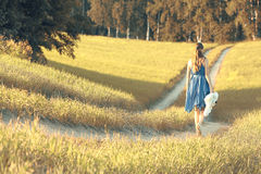 Girl walking along in  field Stock Photos