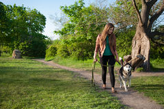 The girl is walking along the footpath with her dog Stock Photo