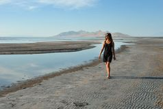 Girl walking along Great Salt Lake beach, Utah. Young woman in short black dress walking on Great Salt Lake shore on a summer day royalty free stock photography
