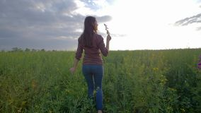 Girl walking along green rapeseed field and enjoying the beauty of nature on background of sky. Girl walking along a green rapeseed field and enjoying the beauty stock footage