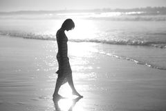 A girl is walking along the ocean Royalty Free Stock Photos