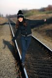 Girl walking along the old rails. Beautiful girl on the old one goes rails royalty free stock photography