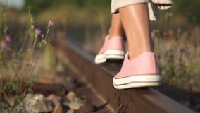 Girl walking along railroad rail. Romantic slow motion tracking shot of young girl feet close-up walking along railroad