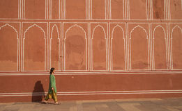 Girl walking along red wall Stock Images