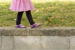 Girl walking along retaining wall Royalty Free Stock Photos