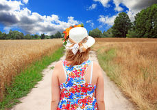 Girl walking along the road in a field Stock Photography