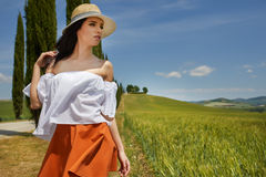 Girl is walking along the road among the fields and a typical Tu. Scan landscape behind her. Tuscany Stock Photos
