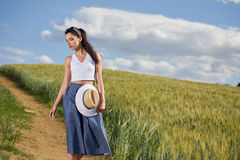 Girl is walking along the road among the fields Royalty Free Stock Photos