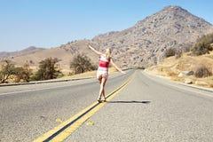 Girl walking along road Royalty Free Stock Photo