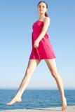 Girl walking along the seashore Stock Photos