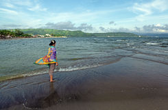 Girl walking along shore Royalty Free Stock Images