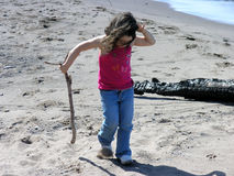 Girl walking along shoreline. A young girl looks at her feet as she walks along a sandy shoreline with a large branch in her hand Royalty Free Stock Image