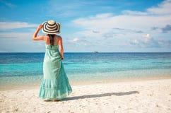 Girl walking along a tropical beach in the Maldive Royalty Free Stock Photos