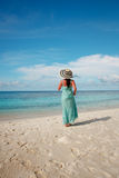 Girl walking along a tropical beach in the Maldives. Stock Photography