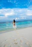 Girl walking along a tropical beach in the Maldives. Stock Photos