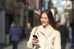 Girl Walking And Texting On The Smart Phone In The Street In Winter Royalty Free Stock Photo