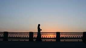 Girl walking around the parapet of embankment in the summer and drinking from a paper Cup. Silhouette in the evening at sunset stock video footage