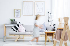Girl walking around room. Girl in white dress walking around modern cozy room with coat rack Stock Photography