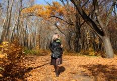 Girl walking in autumn park alley Stock Photo