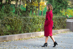 Girl walking autumn. Portrait of an attractive beautiful pretty cute young caucasian thoughtful woman (girl, female, person, model) in red coat walking by an Royalty Free Stock Photos