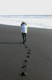 Girl walking away on a beach in Iceland Stock Photography