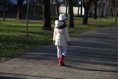 A girl walking away. A girl walking away in park stock photos