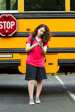 Girl walking away from School Bus while texting on her phone Royalty Free Stock Photos