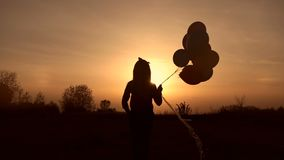 Girl walking with balloons in field at sunset. stock footage