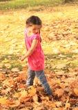 Girl walking barefoot in dead maple leaves Stock Photo