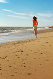 Girl walking on the beach Royalty Free Stock Photography