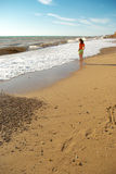 Girl walking on the beach Royalty Free Stock Photos